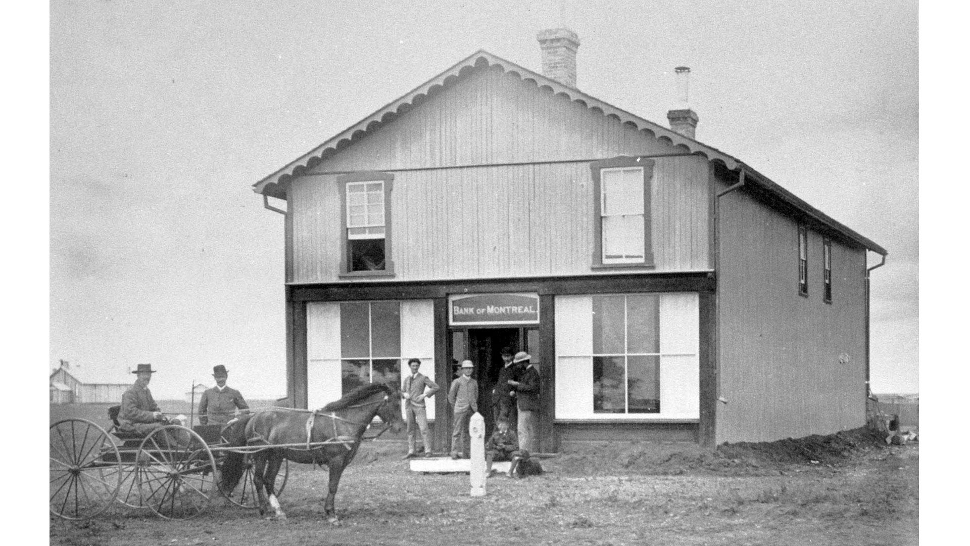 The original Regina branch, 1884, with staff and customers standing on the porch.